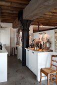 Samovar and silver candelabra on white kitchen counter built around black metal pillar in loft apartment