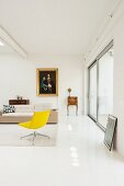 Yellow swivel chair, pale designer sofa, small, antique cabinet and gilt-framed painting on wall in minimalist loft apartment