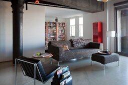 Loungebereich in restauriertem Loft mit historischer Metallsäule