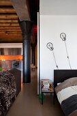 Offener Schlafbereich mit Designerwandleuchten, Blick auf schwarze Metallsäulen und Edelstahlküche in Loftwohnung