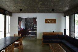 Esstisch und Ecksofa in offenem Wohnbereich mit Betondecke, Hintergrund Durchgang zur Küche