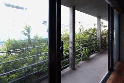 Geöffnete Glasschiebetür zu Balkon mit Stahlgeländer