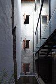 Schmaler, hoher Innenhof mit geöffneten Fensterläden