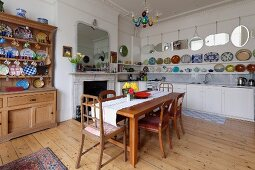 Dining area with wooden table and chairs next to fireplace and dresser; decorative plates and collection of mirrors above kitchen counter