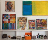 Abstract paintings and portraits on wall and on shelves