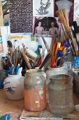 Jars and china pots holding paintbrushes and writing utensils