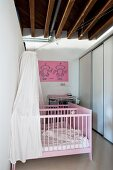 Pink-painted twin cots with white canopies and fitted wardrobes below rustic wood-beamed ceiling