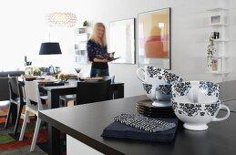 Tassen mit schwarzweissem Muster auf Theke, im Hintergrund Frau an gedecktem Tisch