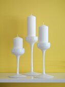White candles in three-piece, white china candlestick set against yellow wall