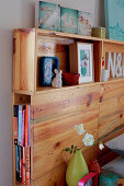 Ornaments on shelves integrated into wooden headboard of double bed