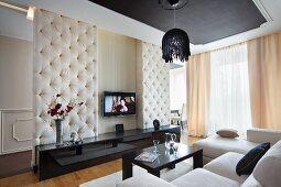 Eleganter Wohnraum mit abgehängter Decke, weisser Sofalandschaft und schwarzem Sideboard vor gepolsterter Raumteilerwand