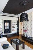 Elegantes Wohnzimmer mit postmodernen Elementen; Hängelampe mit Schlaufenschirm, im Hintergrund ein Einbauregal mit Spiegelnische