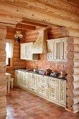 Blick durch Durchgang auf ländliche Küche mit Terrakottaboden in Massivholzhaus