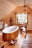Freistehende Badewanne mit Holzeinkleidung auf gefliestem Boden, in holzverkleidetem Dachgeschoss