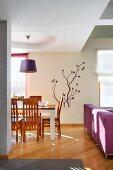 Eleganter Wohnraum mit Essplatz unter Pendelleuchte in kreisförmigem Deckenfeld, im Hintergrund Blumenmotiv auf Wand, Parkettboden mit Diagonalverlegung