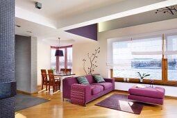 Pinkfarbenes Sofa mit passendem Couchtisch in offenem Wohnraum, im Hintergrund Essplatz, Parkettboden mit Diagonalverlegung
