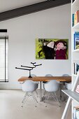 Dining table with solid wooden top and classic shell chairs in loft apartment interior with modern artwork on wall