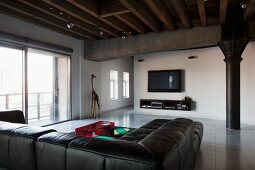 Black leather couch below wood-beamed ceiling and black metal column in industrial-style loft apartment with minimalist furnishings