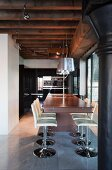 Elegant wooden counter and white swivel bar stools below pendant lamps and spotlights attached to power rail on wood-beamed ceiling in loft apartment with industrial character