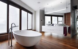 Modern, free-standing bathtub with floor-mounted tap fittings on walnut parquet floor in designer bathroom with floor-to-ceiling, frosted windows