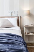 Table lamp on delicate, white bedside table next to bed against white and grey striped wallpaper