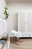 White, designer rocking chair next to painted wardrobe, bouquet of lilies and white storage baskets on open-fronted shelving in corner of bedroom