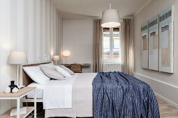 Bedroom with white and grey striped wallpaper, blue blanket on double bed, desk and various lamps