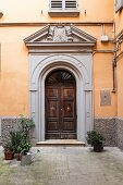 Entrance to traditional, Italian palazzo in courtyard with ochre façade and grey strip along base
