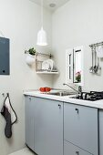 Pale grey kitchen counter below window and plate rack on wall