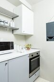 Pale grey kitchen counter with white wall unit and metal shelves