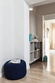 Newspaper on dark blue pouffe and open-fronted shelves in hallway