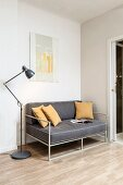 Delicate, grey sofa with ochre scatter cushions and retro standard lamp in corner