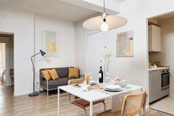 Small dining table, cantilever chairs and delicate, grey sofa in living area