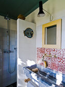 Trough-style sink below wall tiles with red and white pattern of circles and shower area behind partition in rustic bathroom