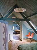 Bedroom in converted attic with wood panelling painted blue and grey