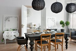 Eclectic, elegant dining room in black and white colour scheme with artworks leaning against walls and period ambiance