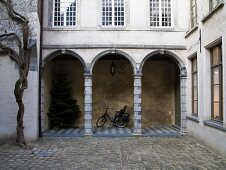 Cobbled courtyard with arcades on ground storey of traditional Flemish town house
