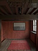 Rug on wooden floor and picture on rusty red wall in minimalist, rusty interior