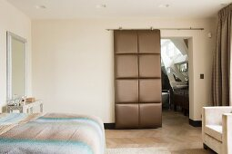 Double bed and open, upholstered sliding door leading to ensuite bathroom in bedroom