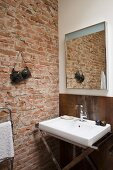Sink with chrome base frame next to exposed brick wall