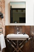 Washstand with chrome frame against rusty, Corten steel wall and below mirror in corner of bathroom