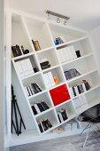 Gekipptes Bücherregal an Wand gebaut, davor teilweise sichtbarer Schalenstuhl