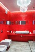 Bad in Rot - Wände und Waschtischablage mit roten Mosaikfliesen, an Decke kugelförmige Pendelleuchte aus aufgehängten Glassteinen