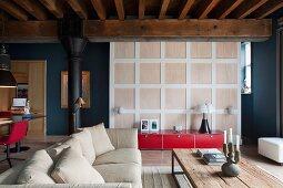 Sitzbereich mit Sofa und rustikalem Tisch in umgenutztem Industrieloft; rotes Lowboard vor Raumteiler Kassettenwand zum Schlafbereich