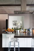 Counter protruding from free-standing, designer kitchen counter with bar stools in loft apartment