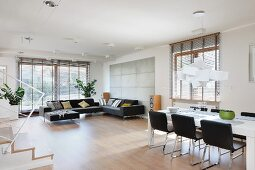 Spacious, open-plan interior; dining area with black chairs below designer light and comfortable lounge area in front of floor-to-ceiling windows