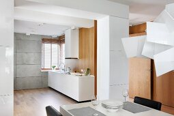 View across dining table in open-plan kitchen with white, minimalist counter and matching extractor hood against wooden wall