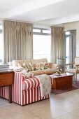 Red and white striped sofa and pale sofa around wooden trunk in front of floor-length curtains on glass wall in living room