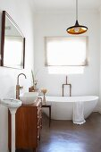 Purist tap fittings, designer bathtub, washstand with drawers, mirror, scales and retro-style light fitting in bathroom
