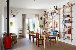 Books on light shelving, retro chairs with different coloured seat cushions around dining table, red log burner and floral sofa